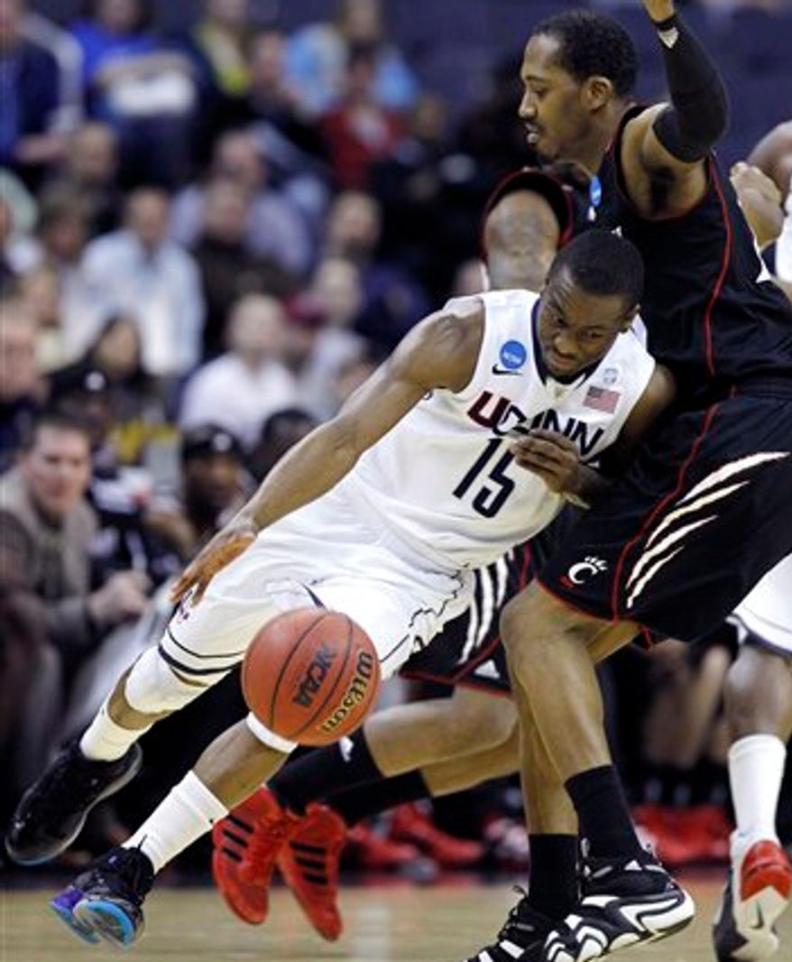 Connecticut guard Kemba Walker (15) drives into Cincinnati forward Darnell Wilks during the first half of the West Regional third-round NCAA tournament college basketball game, Saturday, March 19, 2011, at the Verizon Center in Washington. (AP Photo/Alex Brandon)