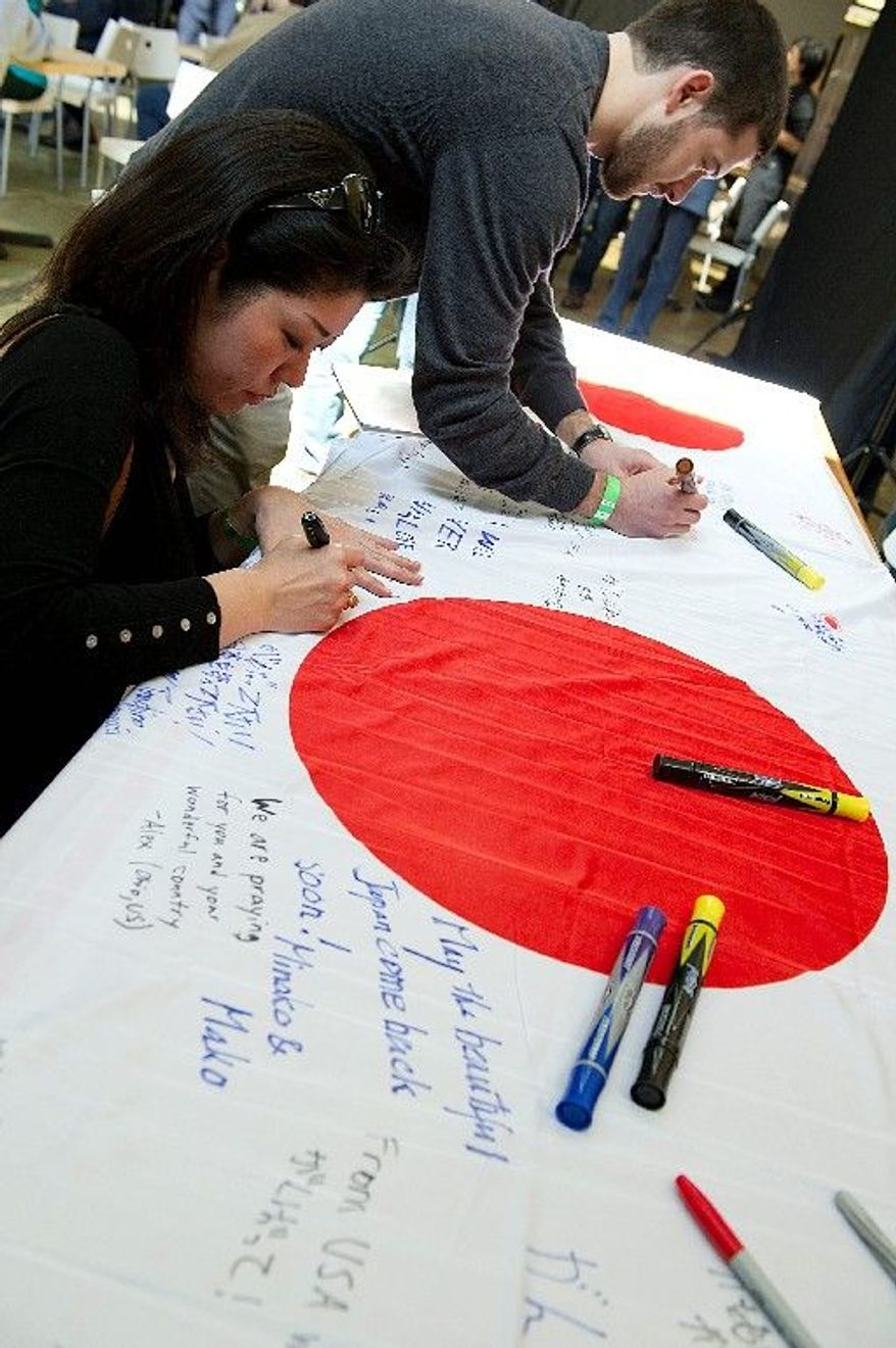 Rina Hirano (left), a Japanese Embassy worker, and Ian Rinehart, a George Washington University graduate student, write messages of support on Japanese flags at the fundraiser Sunday at Cafe Asia in Arlington. (Barbara L. Salisbury/The Washington Times)