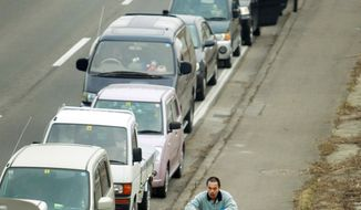 A bicyclist passes hundreds of motorists lining a Fukushima highway in hopes of filling their gas tanks. Massive shortages continue, and Fukushima residents are wondering whether they will ever be able to live again in areas around radiation leakages. (Associated Press)