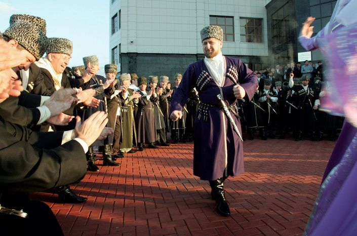** FILE ** Ramzan Kadyrov, clad in a traditional Chechen costume, dances in Chechnya's provincial capital, Grozny. He has described himself as a protector of Russia's unity, but Chechens live in fear of his authoritarian rule. (Associated Press)