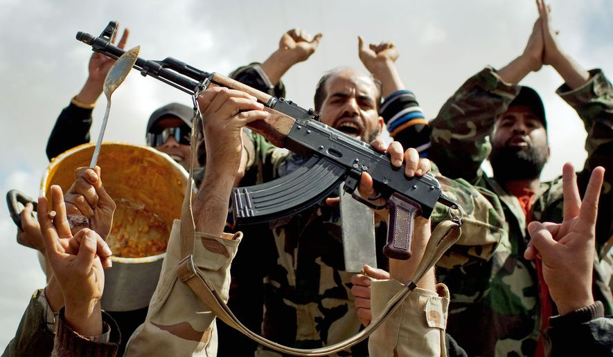 REVOLUTION: Libyan rebels celebrate with a pot of beans left behind by Moammar Gadhafi's forces when they retreated on the outskirts of Benghazi in eastern Libya on Sunday. The U.S. military said 112 Tomahawk cruise missiles were fired from American and British ships and submarines at more than 20 coastal targets to clear the way for air patrols to ground Libya's air force. (Associated Press)