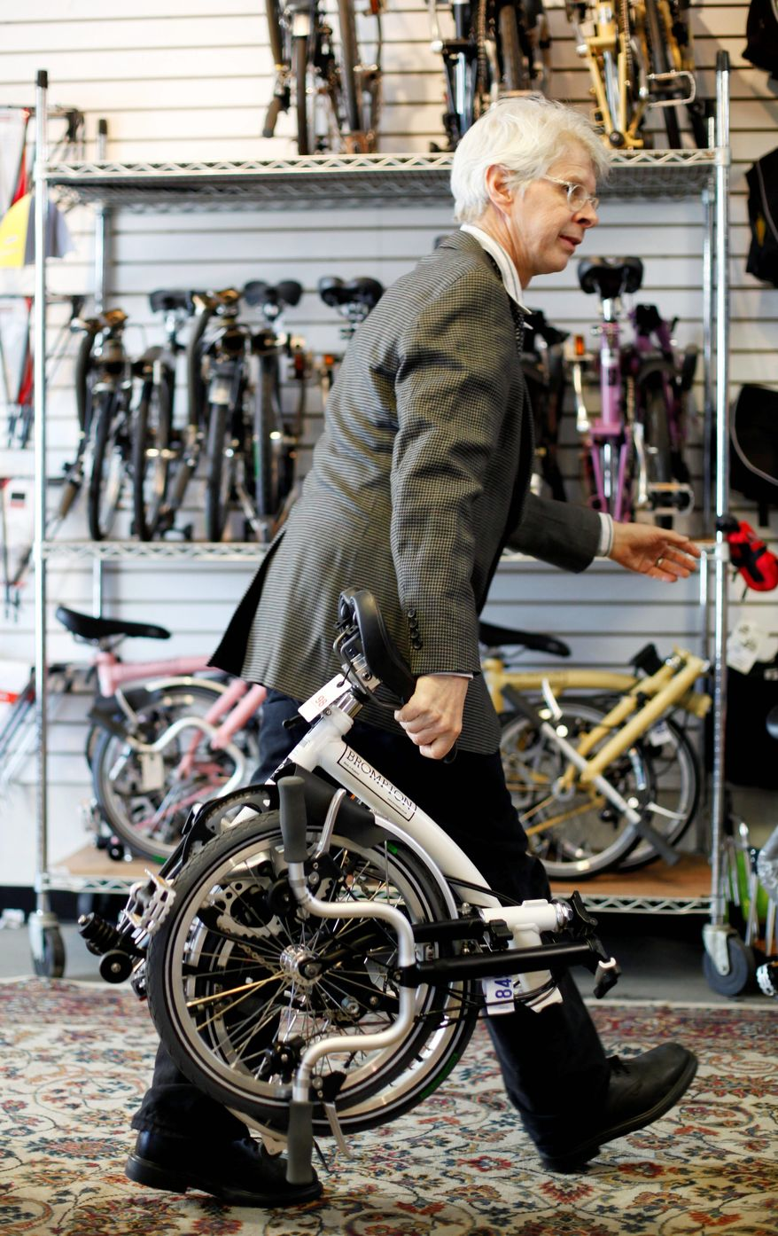 """""""It's light, it's fast. It has a quirky charm. It's tanklike but incredibly high-tech,"""" Michael McGettigan says about the Brompton bicycle. His shop was one of the first in the U.S. to sell the British bikes. (Associated Press)"""
