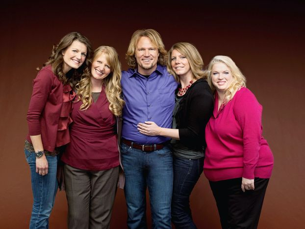 """** FILE ** Kody Brown hugs his wives, (from left) Robyn, Christine, Meri and Janelle. They appear on the reality series """"Sister Wives"""" on TLC. """"'Sister Wives' shows that polygamy is rather boring,"""" said Brian Barnard, a Utah-based religious-freedom lawyer. (Associated Press)"""