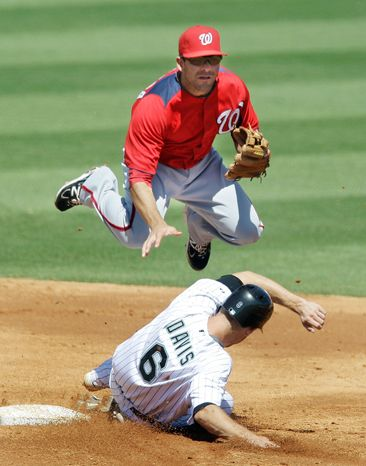 Todd Anderson/Special to The Washington Times Washington Nationals second baseman Danny Espinosa (left), jumping over Florida Marlins runner Brad Davis (6) during an exhibition game, has developed a chemistry with shortstop Ian Desmond (right) after adapting to the position.
