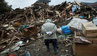 An elderly Japanese woman searches for her belongings Monday in the quake- and tsunami-destroyed town of Rikuzentakata in northeastern Japan. (Associated Press)