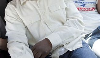 "With a bandage in his right hand, Haitian-American singer Wyclef Jean, front, sits inside a car before casting his ballot at a polling station during a presidential runoff in Port-au-Prince, Haiti, Sunday, March 20, 2011. Jean told the AP in a telephone interview  he was grazed by a bullet in the hand when he stepped out of his car in Haiti to make a phone call. Haiti's voters will choose between candidates Mirlande Manigat, the former first lady, and Michel ""Sweet Micky"" Martelly, a star of Haitian music to lead the country.  (AP Photo/Ramon Espinosa)"