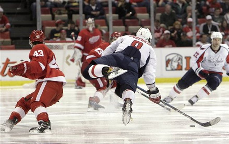 Washington Capitals left wing Alex Ovechkin (8), of Russia, goes airborne while trying to shoot against the Detroit Red Wings in the third period of an NHL hockey game in Detroit,  Wednesday, March 16, 2011. Detroit won 3-2. (AP Photo)