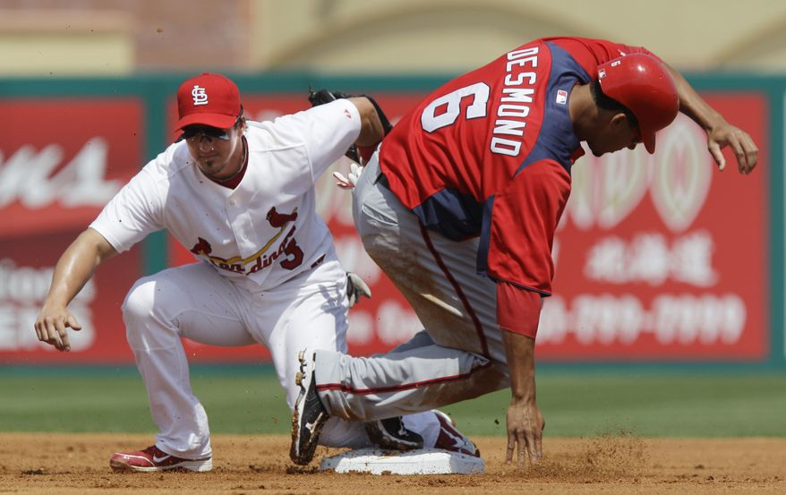 Washington Nationals' Ian Desmond (6) is tagged out by St. Louis Cardinals shortstop Ryan Theriot (3) during a steal attempt in the first inning of a spring training baseball game, Monday, March 21, 2011 in Jupiter, Fla. (AP Photo/Carlos Osorio)