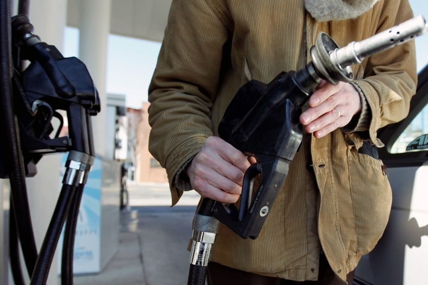 A motorist in Philadelphia returns the nozzle to the pump after filling up recently. Oil prices rose above $104 per barrel Tuesday as traders continue to focus on international crises driving supply and demand. (Associated Press)