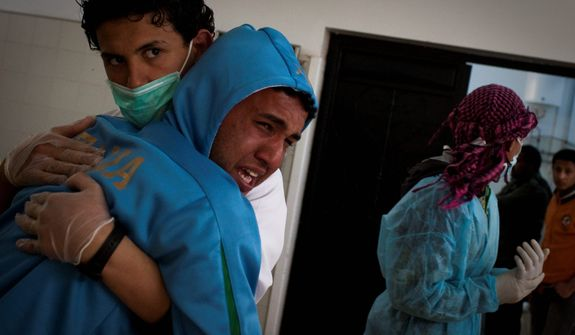 A Libyan is comforted Tuesday by a hospital staffer after identifying his brother in the morgue in Benghazi. The man's brother had been killed in fighting around the city of Ajdabiya. (Associated Press)