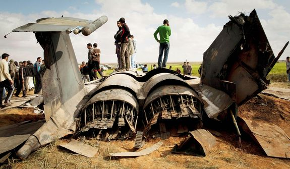 Libyans inspect the wreckage of a U.S. F-15E fighter jet after it crashed Tuesday in a field east of Benghazi. Both crew members ejected and were rescued. The U.S. Africa Command blamed mechanical failure for the loss of the aircraft. (Associated Press)