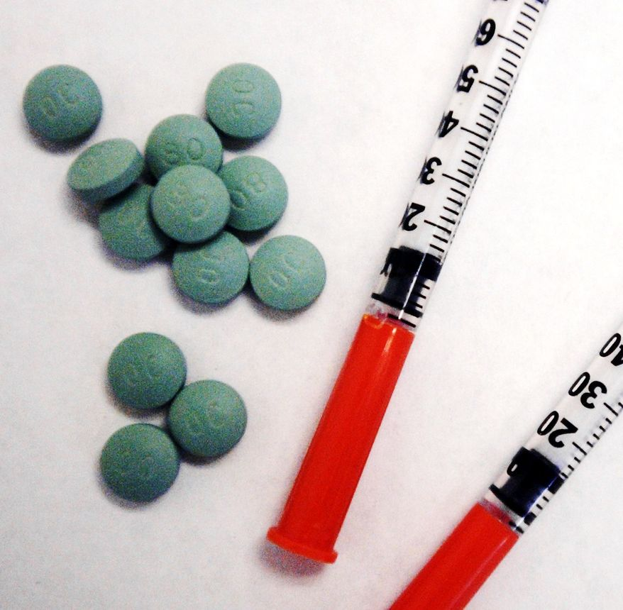 **FILE** A handful of 80-milligram Oxycontin pills and two syringes are seen here on a table in Fairfax, Va., on Aug. 15, 2003. (Rod A. Lamkey Jr./The Washington Times)