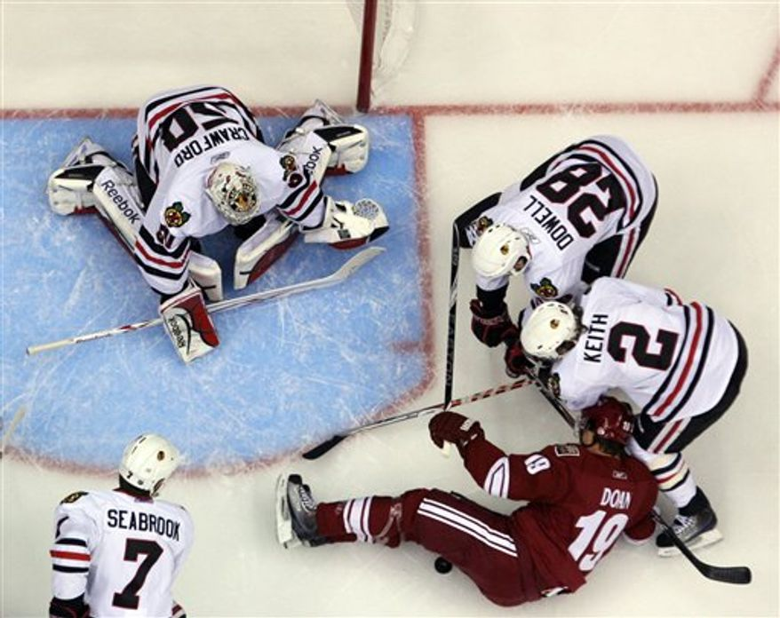 Phoenix Coyotes' Shane Doan, bottom right, has the puck caught beneath his legs as Chicago Blackhawks goalie Corey Crawford, top, defensemen Jake Dowell (28) Duncan Keith (2) and Brent Seabrook (7) defend during the first period of an NHL hockey game Sunday, March 21, 2011, in Glendale, Ariz. (AP Photo/The Arizona Republic, Emmanuel Lozan)  MARICOPA COUNTY OUT; MAGS OUT; NO SALES