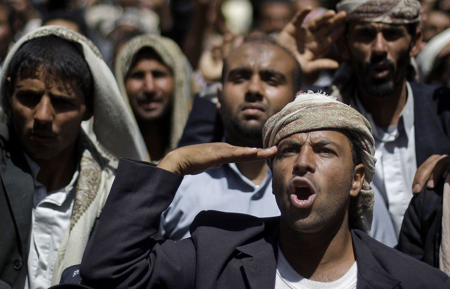 An anti-government protester salutes Yemeni army soldiers who joined them during a demonstration demanding the resignation of President Ali Abdullah Saleh in Sanaa, Yemen, on Monday, March 21, 2011. (AP Photo/Muhammed Muheisen)