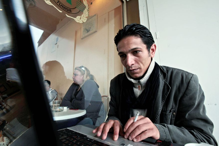 """Wissem Zghaier, who was beaten and tortured during the Tunisian uprising, works on his laptop in a coffee shop March 16 in Tunis. He sees blogging activists as """"the first line of defense of freedom."""" (Associated Press)"""