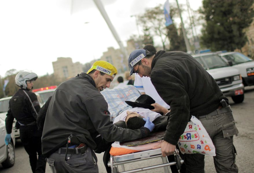 Israeli rescue workers and paramedics treat an injured man after an explosion near a bus stop in Jerusalem on Wednesday. The bomb killed one and wounded scores in what appeared to be the first militant attack in the city in nearly three years. (Associated Press)