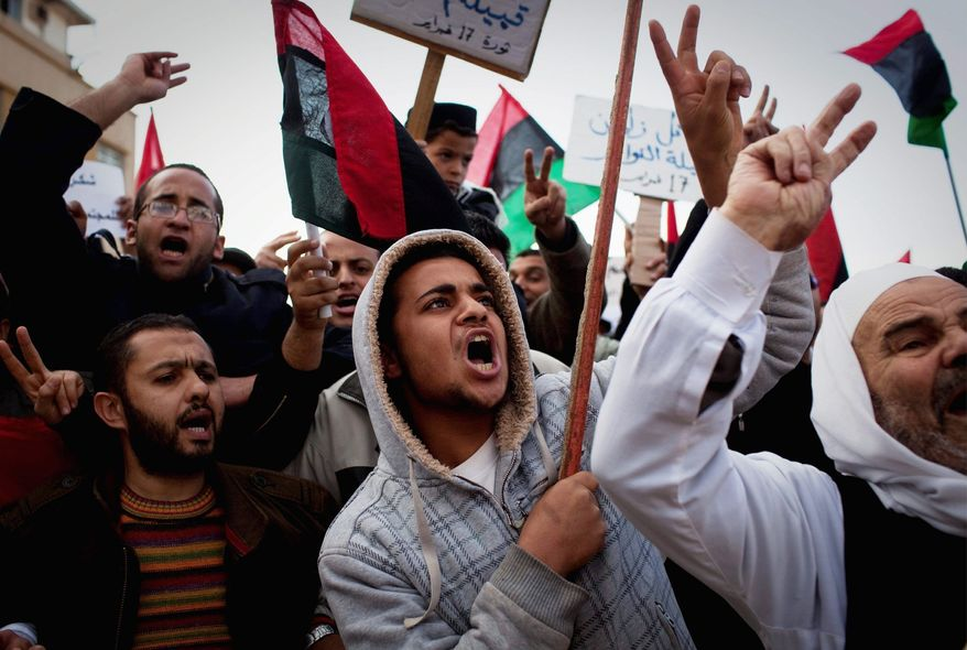 Libyan protesters chant as they join a rally in support of the allied air campaigns against the troops of Col. Gadhafi in Benghazi. Pro-Gadhafi forces have used tanks, artillery and rocket launchers against unarmed civilians and a rag-tag rebel army in recent days. (Associated Press)