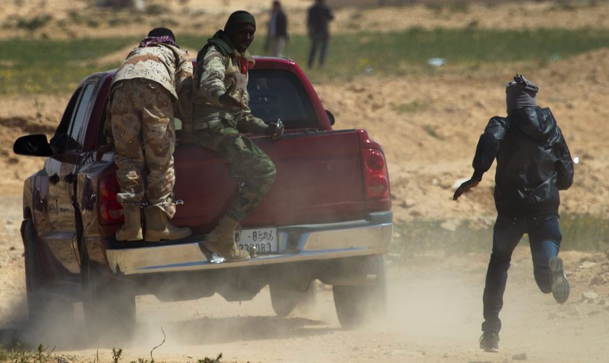 Libyan rebels run to take cover as mortars from Col. Moammar Gadhafi's forces are fired on the front line near Zwitina on the outskirts of Ajdabiya in eastern Libya on Wednesday. Coalition attack planes have started to strike Col. Gadhafi's forces in and around the rebel-held towns of Ajdabiya and Misurata. (Associated Press)
