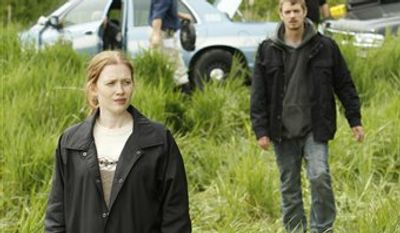 """In this publicity image released by AMC, Mireille Enos portrays Detective Sarah Linden, right, and Joel Kinnaman portrays Detective Stephen Holder in a scene from the AMC original series """"The Killing,"""" premiering April 3, 2011 at 9 p.m. EST. (AP Photo/AMC, Chris Large)"""