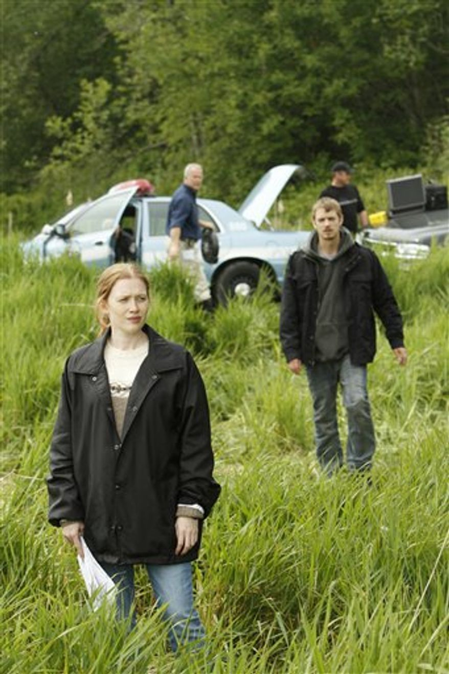 "In this publicity image released by AMC, Mireille Enos portrays Detective Sarah Linden, right, and Joel Kinnaman portrays Detective Stephen Holder in a scene from the AMC original series ""The Killing,"" premiering April 3, 2011 at 9 p.m. EST. (AP Photo/AMC, Chris Large)"