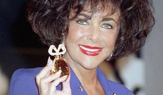 ** FILE ** This Sept. 11, 1991, file photo shows actress Elizabeth Taylor as she holds a $100,000 special edition of her new White Diamonds fragrance at a news conference in New York. Taylor died Wednesday at age 79 of congestive heart failure. (AP Photo/Richard Drew, FILE)