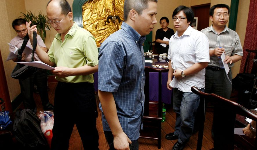 Legal scholar Xu Zhiyong (center) is met with other Chinese lawyers, including Mr. Jiang (right), in a Beijiing restaurant in July 2009. Later that month, Mr. Xu was detained on charges of tax evasion; the charges were dismissed a year later and he was freed. (Associated Press)