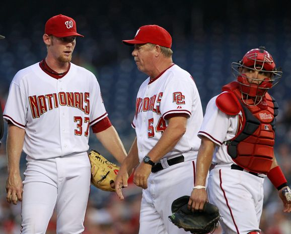 Stephen Strasburg, talking to pitching coach Steve McCatty, was the story of 2010, first for his domination and then for his injury. With the former No. 1 pick gone for the season, the rotation has a few more question marks. (Associated Press)