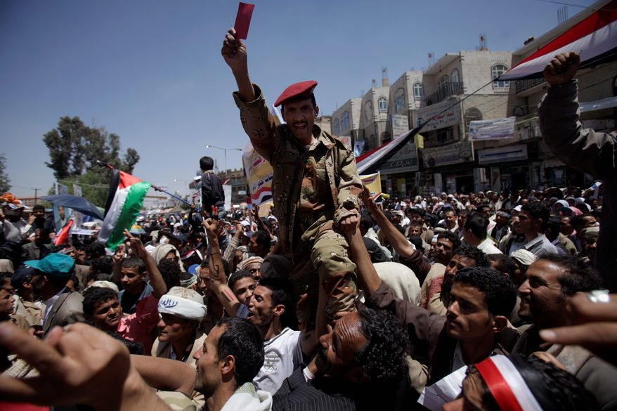 A Yemeni army officer lifted by anti-government protesters reacts as he joins a demonstration demanding the resignation of longtime Yemeni President Ali Abdullah Saleh, in Sanaa, Yemen, on Thursday. (Associated Press)