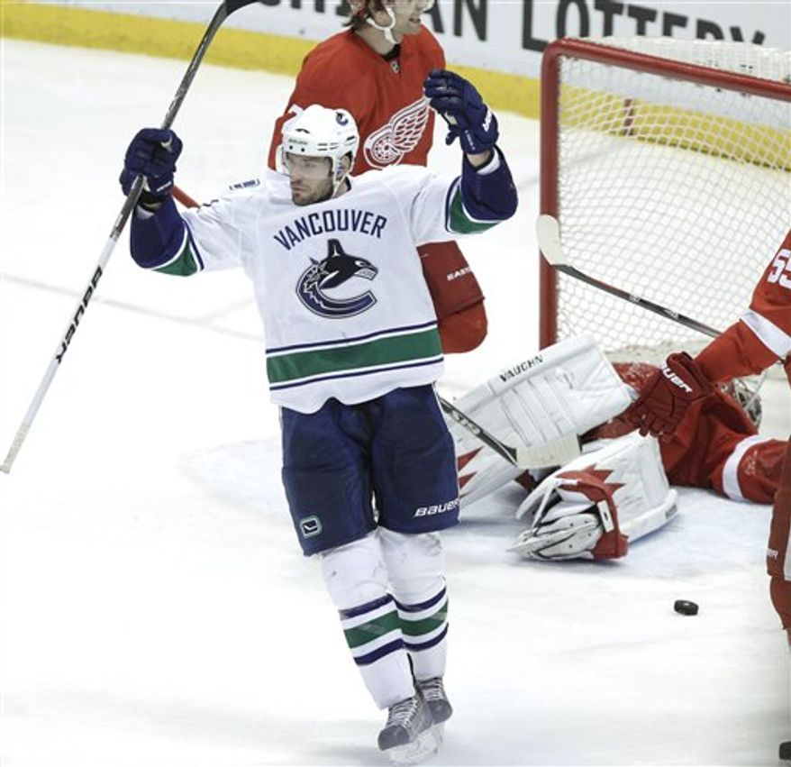 Vancouver Canucks center Ryan Kesler (17) celebrates a Daniel Sedin, not visible, goal against Detroit Red Wings goalie Jimmy Howard (35) in the third period of an NHL hockey game in Detroit, Wednesday, March 23, 2011. Vancouver won 2-1. (AP Photo/ Paul Sancya)