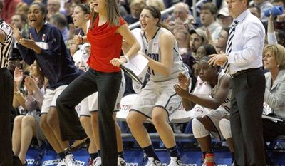 FILE - In this Dec. 21, 2010 file photo, Connecticut's Caroline Doty, second from left in red, celebrates alongside teammates and coach Geno Auriemma, right, as time winds down in Connecticut's 93-62 win over Florida State in an NCAA basketball game in Hartford, Conn., to set the NCAA record with 89 consecutive wins. Doty, who  missed playing the entire season while recovering from a third tear to the anterior cruciate ligament in her left knee, remained with her teammates as they pursued their third straight national championship.  (AP Photo/Bill Sikes, File)