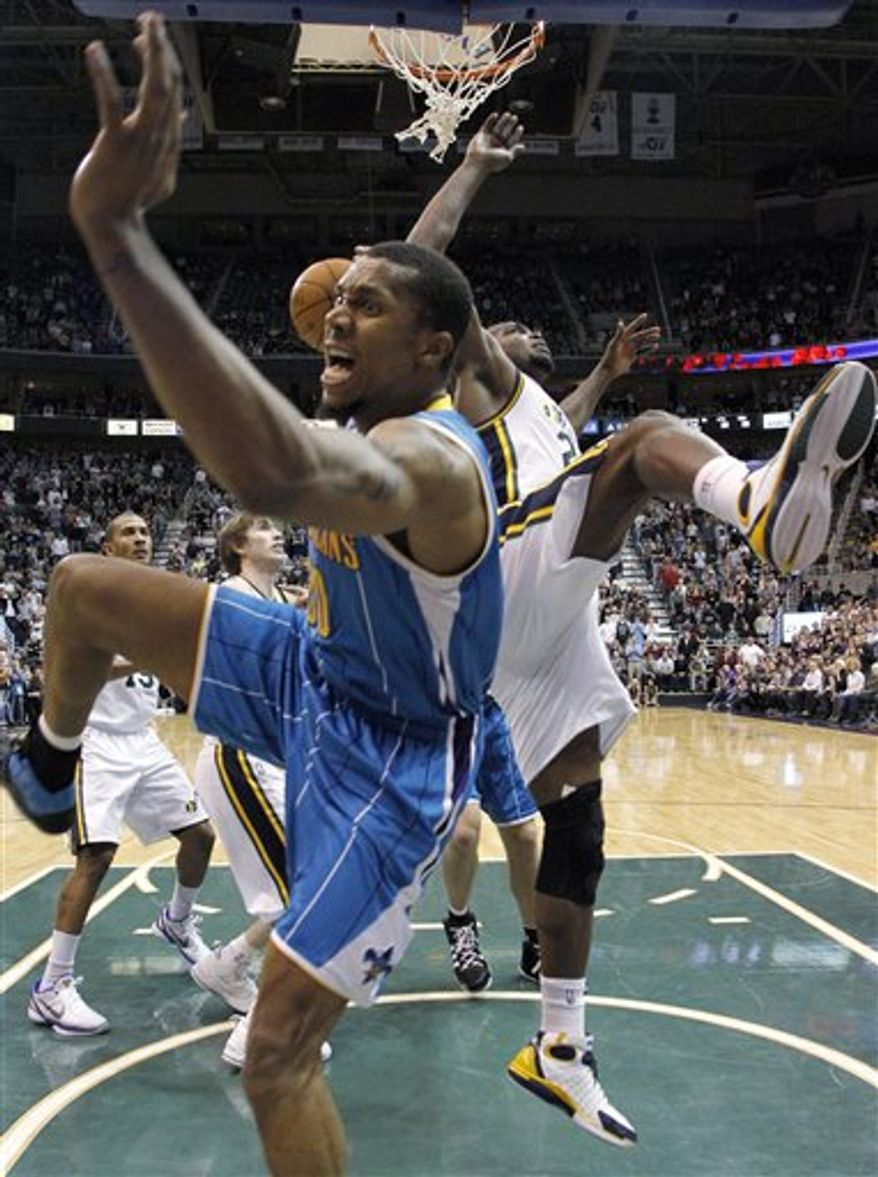 New Orleans Hornets forward David West, left, falls out of bounds as he is defended by Utah Jazz forward Paul Millsap, right, during the second half of an NBA basketball game Thursday, March 24, 2011, in Salt Lake City. West was hurt on the play and was taken off in a wheelchair. The Hornets won 121-117. (AP Photo/Jim Urquhart)
