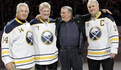 FILE - In this Feb. 23, 2011 file photo, Buffalo Sabres new owner Terry Pegula, second from right, poses with former Sabres players Rene Robert (14), Rick Martin (7) and Gilbert Perreault (11) before an NHL hockey game against the Atlanta Thrashers in Buffalo, N.Y.  Buffalo is set to honor one of the city's most popular sports figures. A public memorial service is planned Thursday, March 24, 2011 for Rick Martin,  who died of heart disease March 13. (AP Photo/David Duprey, File)