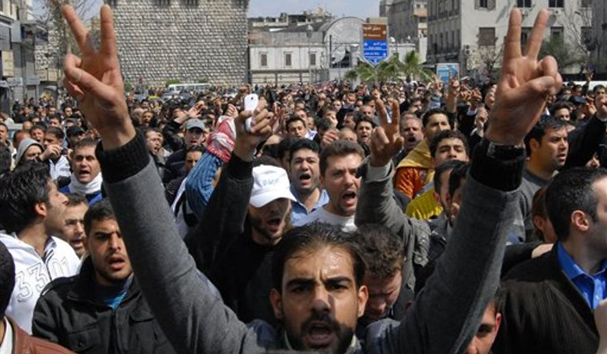 Anti-Syrian government protesters shout slogans as they protest after Friday prayers in Damascus, Syria, Friday, March 25, 2011. Thousands of Syrians took to the streets Friday demanding reforms and mourning dozens of protesters who were killed during a violent, week long crackdown that has brought extraordinary pressure on the country's autocratic regime, activists and witnesses said. (AP Photo/Muzaffar Salman)
