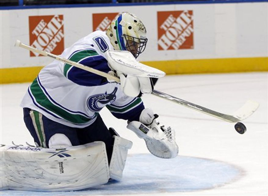 Atlanta Thrashers defenseman Zach Bogosian (4) is checked into the boards by Vancouver Canucks left wing Christopher Higgins (20) in the second period of an NHL hockey game  Friday,  March 25, 2011 in Atlanta.  (AP Photo/John Bazemore)