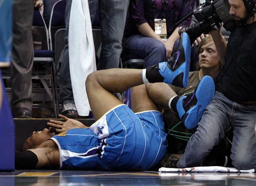 New Orleans Hornets forward David West (30) lies on the baseline after being injured during the second half of an NBA basketball game against the Utah Jazz on Thursday, March 24, 2011, in Salt Lake City. West was taken off the court in a wheelchair. The Hornets won 121-117. (AP Photo/Jim Urquhart)