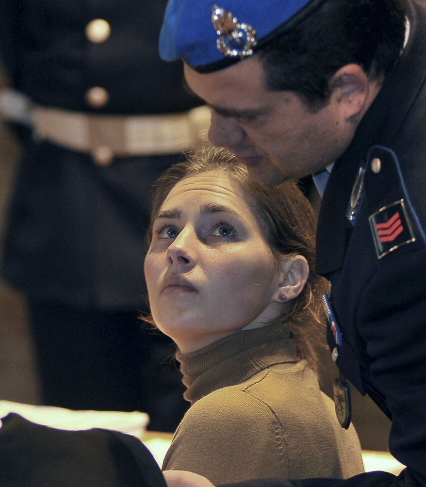 Amanda Knox looks up at a police officer as she sits in court in Perugia, central Italy, Saturday, March 26, 2011, during her appeals trial. Knox was convicted of murdering her British roommate in Perugia, Meredith Kercher, and sentenced to 26 years in prison. (AP Photo/Stefano Medici)