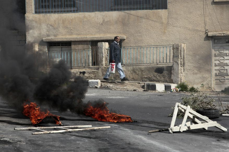 A Syrian man, passes burning tires and a roadblock set by anti-Syrian government protesters, following clashes between the Syrian security forces and protesters, in the southern city of Daraa, Syria, Wednesday March 23, 2011. Syrian security forces shot live ammunition and tear gas early Wednesday near a mosque where protesters have been camped out in southern Syria, killing six people including a paramedic, activists said. The early morning attack near the al-Omari mosque in the southern city of Daraa marks the deadliest single day since anti-government protests inspired by uprisings across the Arab world reached this country last week. The latest deaths brings the number of people killed in Daraa since Friday to at least 13. (AP Photo/Hussein Malla)