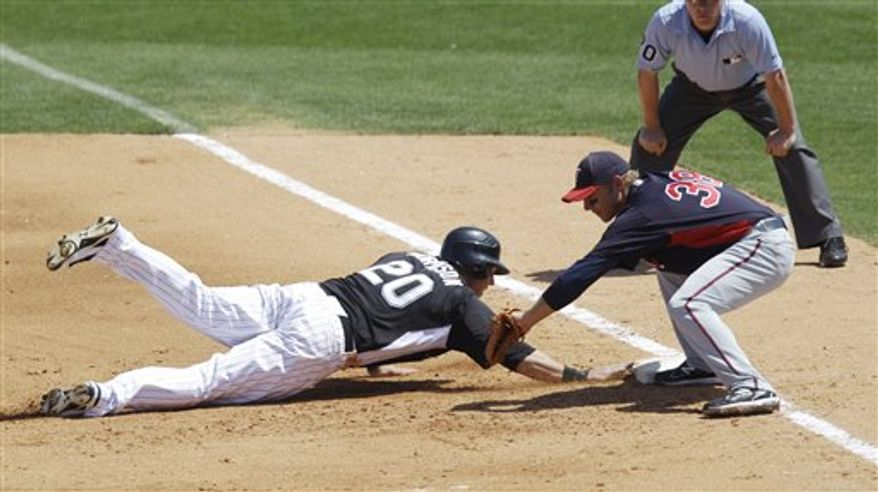 Florida Marlins' Logan Morrison (20) safely gets back under the tag of Minnesota Twins first baseman Luke Hughes (38) during the fourth inning of a spring training baseball game, Tuesday, March 22, 2011, in Jupiter, Fla. (AP Photo/Carlos Osorio)
