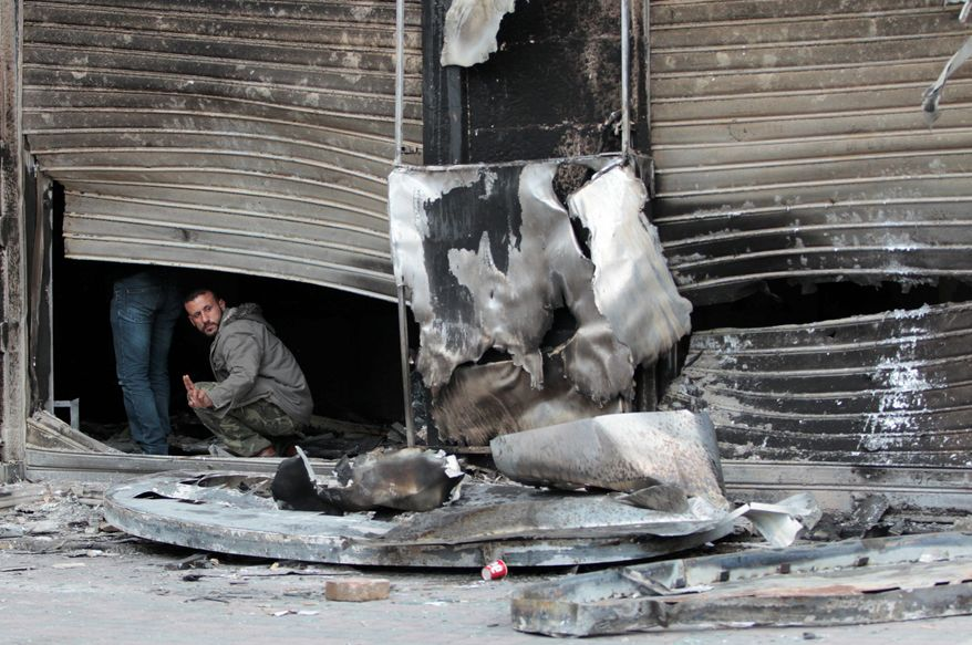 A Syrian emerges Sunday from what remains of a shop destroyed during clashes between security forces and anti-government protesters in Latakia, Syria. Latakia is a Mediterranean port once known as a summer tourist attraction. (Associated Press)