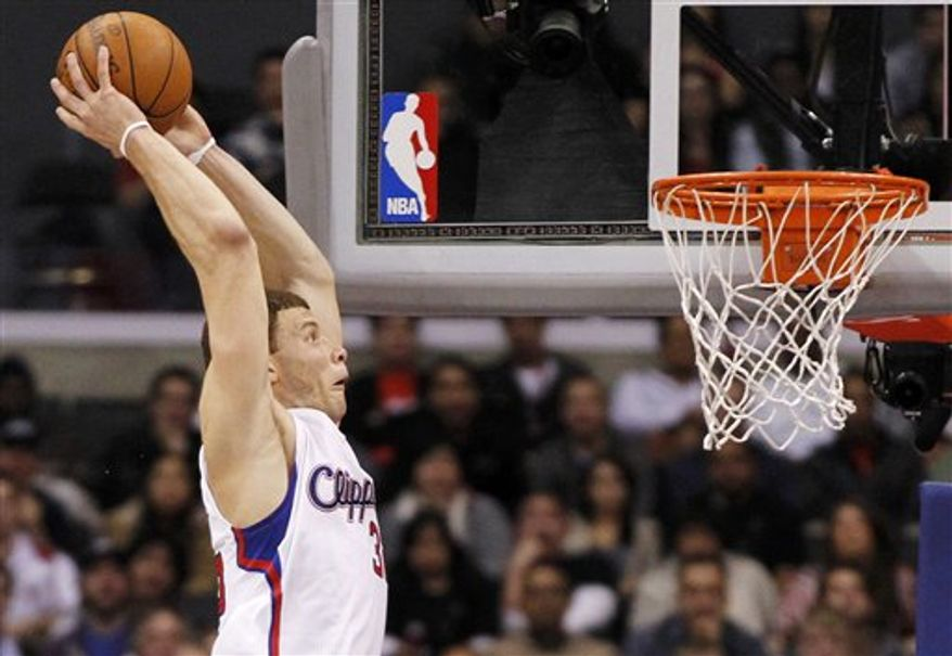 Toronto Raptors' James Johnson, right, is fouled by Los Angeles Clippers' DeAndre Jordan, left, during the first quarter of an NBA basketball game in Los Angeles on Saturday, March 26, 2011. (AP Photo/Danny Moloshok)
