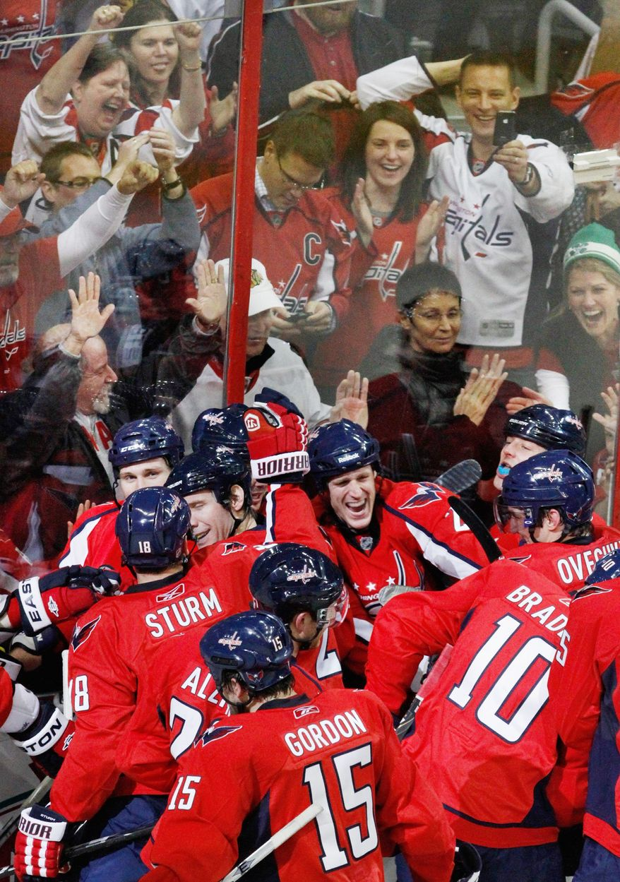 Associated Press Fans cheer as the playoffs-bound Washington Capitals celebrate an overtime win over the Chicago Blackhawks at the Verizon Center on March 13.