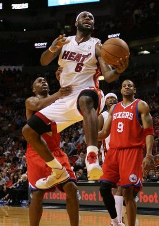 Miami Heat's Lebron James (6) drives to the basket as Philadelphia 76ers' Jodie Meeks left, and Andre Iguodala (9) defend during the first quarter of an NBA basketball game in Miami, Friday, March 25, 2010. (AP Photo/Jeffrey M. Boan)