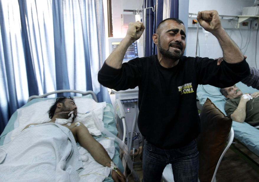 A Syrian man (right) reacts to the wounding of his brother (left), who was seriously injured during violence between security forces and armed groups in Latakia, northwest of Damascus, Syria, on Sunday, March 27, 2011. (AP Photo/Hussein Malla)