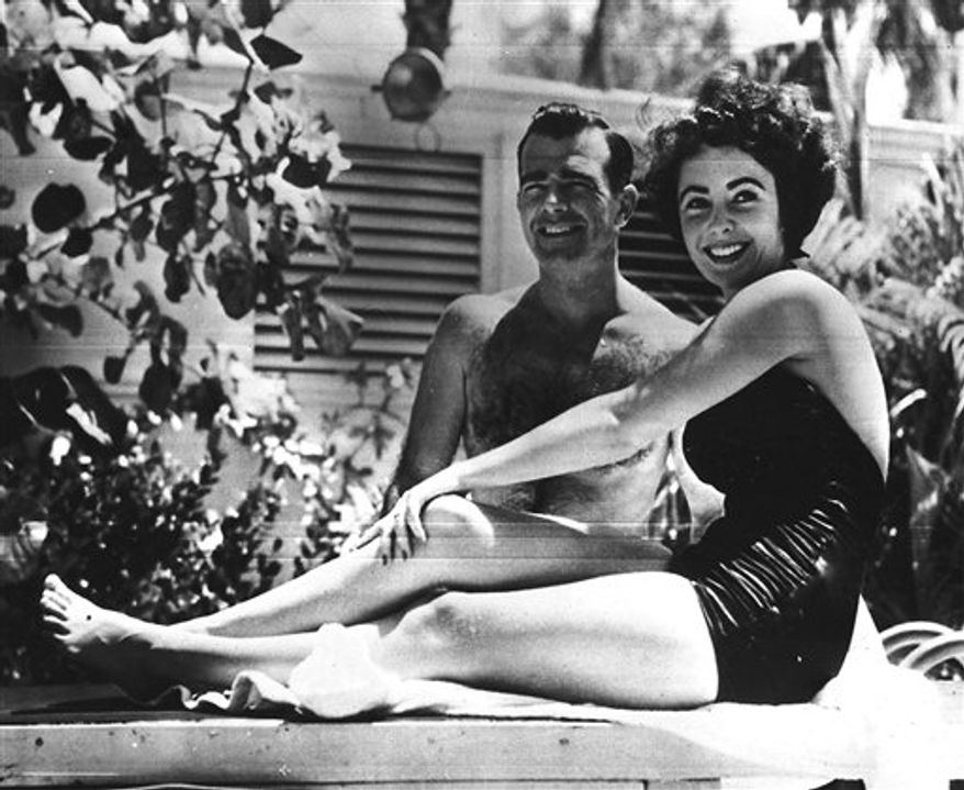 FILE - In this June 7, 1949 file photo, 17-year-old actress Elizabeth Taylor, right,  poses with fiance William D. Pawley Jr.  at his father's home in Miami Beach, Fla. Over 60 love letters written by the late actress will be put up for auction by RR Auction in Amherst, N.H. The auction house bought the letters two years ago from William Pawley, who was engaged to Taylor for less than a year in 1949. Taylor died Wednesday, March 23, 2011 in Los Angeles of congestive heart failure at age 79.   (AP Photo, file)
