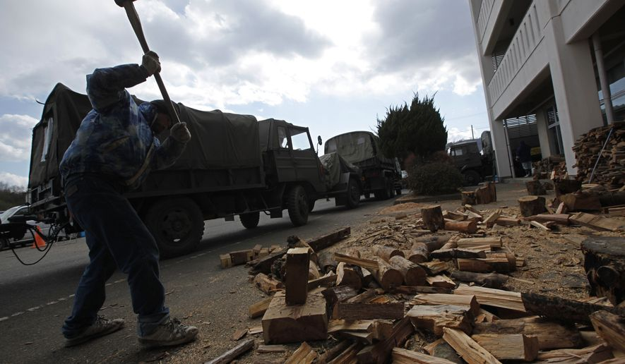 A survivor of the earthquake and tsunami in Japan cuts woods for fire for warmth at a shelter in the devastated town of Yamamoto, Miyagi Prefecture, in northeastern Japan on Monday, March 28, 2011. (AP Photo/Vincent Yu)