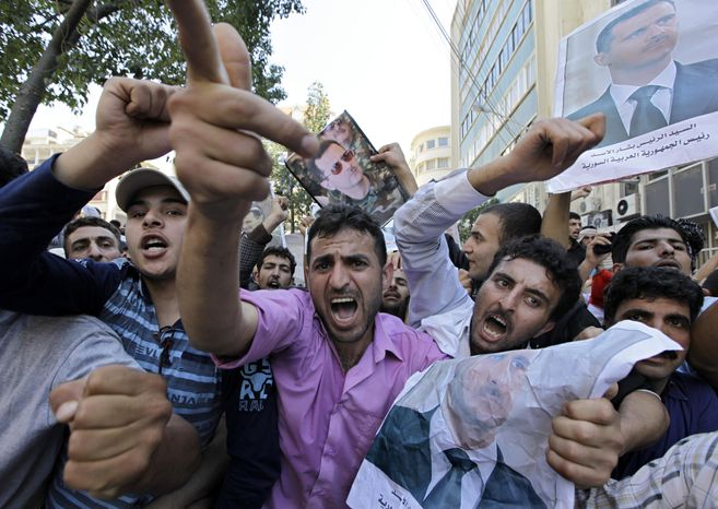 Supporters of Syrian President Bashar Assad shout slogans as they carry pictures of the president during a sit-in in front of the Syrian Embassy in Beirut on Sunday, March 27, 2011. (AP Photo/Bilal Hussein)