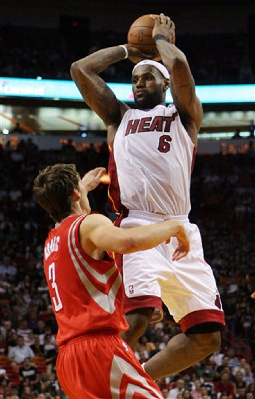 Miami Heat's Lebron James (6) controls the ball as Houston Rockets' Goran Dragic (3) defends during the first quarter of an NBA basketball game in Miami, Sunday, March 27, 2011. (AP Photo/Jeffrey M. Boan)