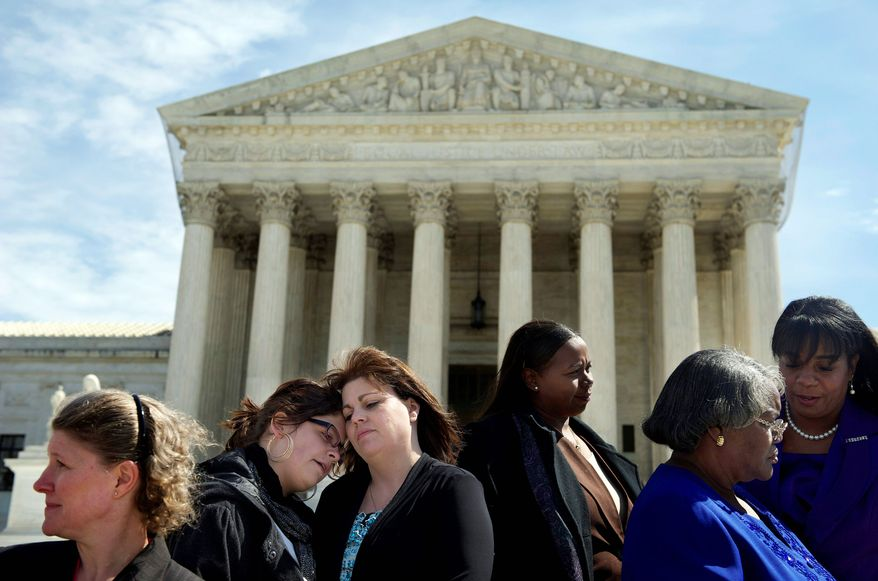 Stephanie Odle, of Norman, Okla., hugs daughter Sydney, 14, on the steps of the Supreme Court on Tuesday as the nation's high court hears arguments as to whether plaintiffs will be allowed to bring a class-action discrimination suit against Wal-Mart, the nation's largest retailer. (Rod Lamkey Jr./The Washington Times)
