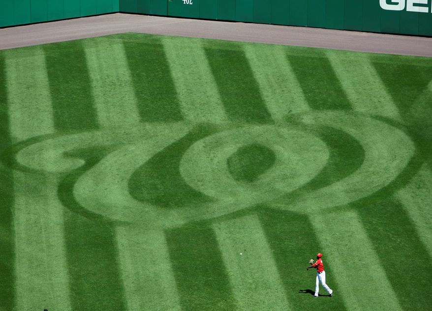 Washington Nationals center fielder Roger Bernadina warms up near the Nationals logo on the grass before a baseball game with the Florida Marlins at Nationals Park in Washington Saturday, April 18, 2009.(AP Photo/Alex Brandon)