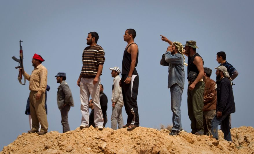 Libyan rebels watch shelling near Bin Jawaad, east of Col. Moammar Gadhafi's hometown of Sirte. Rebels say loyalist forces rape to terrorize opponents of Col. Gadhafi's regime. Almost all of the victims of sexual assault who have gone to hospitals have said they were attacked by the regime's soldiers. (Associated Press)